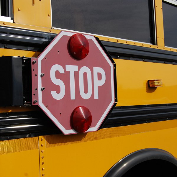 A yellow school bus with a red stop sign