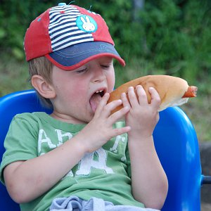 A young boy in a baseball cap eating a hot dog