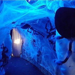 A giant spider crawls through the cobwebs inside the haunted house