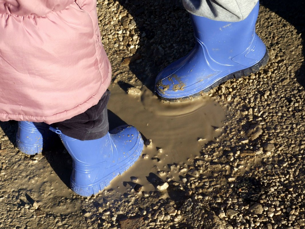 Two kids playing in a mud puddle in blue gumboots