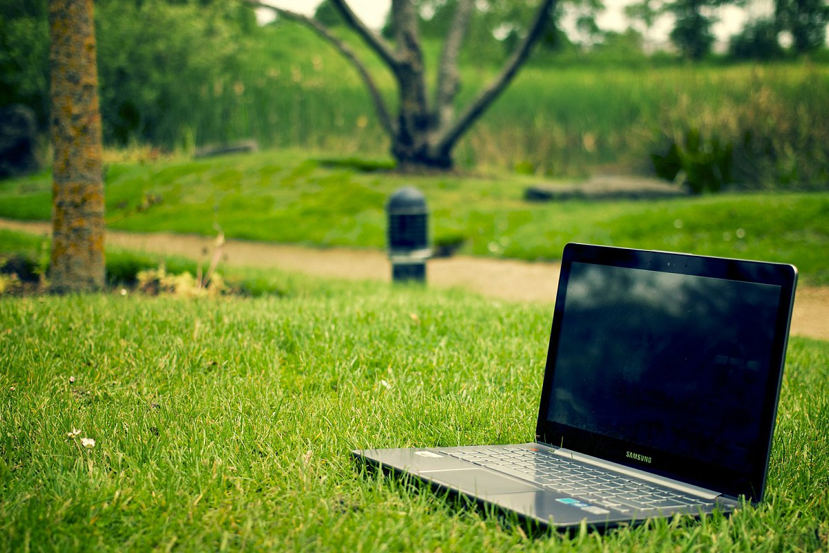A laptop sitting outside in the grass